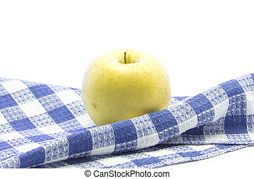 Fresh yellow apple healthy fruit on folded blue tablemat and...