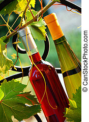Wine bottles between vine leaves - red and white wine...