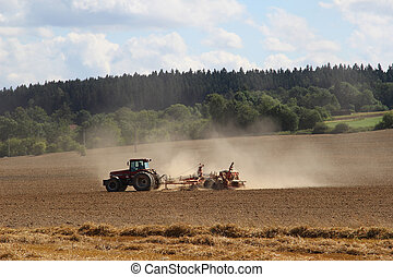 Tractor - Agricultural tractor goes through the field to...