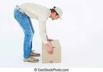 Delivery man picking cardboard box - Full length side view...