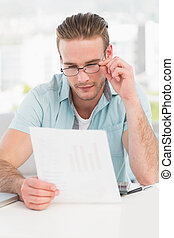 Businessman reading document at his desk in his office