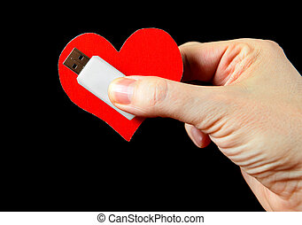 Heart Shape and USB Drive in the Hand on the Black...