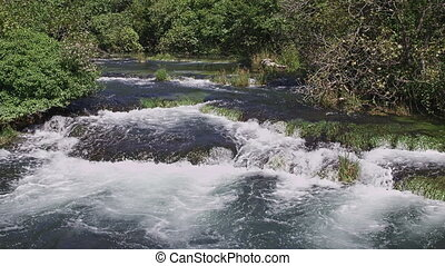 Krka river cascade - River creates a cascade flowing through...