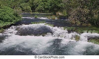 Krka river cascade - River creates a cascade flowing through...