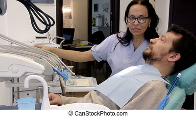 Man getting ready for operation - Female dentist talking to...