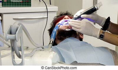 Man getting teeth whitening operation - Man being operated...