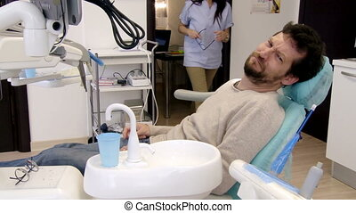 Man having teeth whitening operatio - Female dentist...