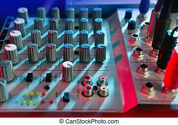 Audio mixer music desk under colorful lights equipment