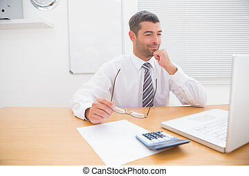 Businessman looking his laptop at his desk