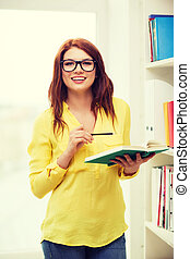 female student in eyeglasses with book and pencil -...