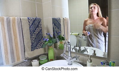 Woman using skincare product - Woman applying moisturizer to...
