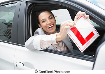 Smiling female driver tearing up her L sign in her car