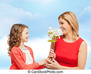 happy little daughter giving flowers to her mother - people,...