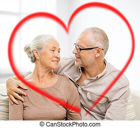 happy senior couple hugging on sofa at home - family,...