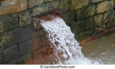Hot Spring Water Flow from Pipe on Wall, closeup