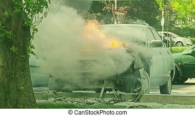 Car engulfed in flames with lot of smoke on the parking lot...