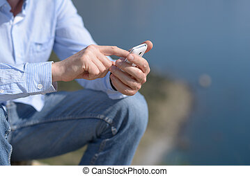 Smartphone - Man with smartphone outdoors. Focus on the...