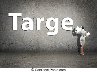 young businesswoman adds target word on concrete wall