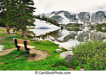 Bench on the lake in Snowy Range Mountains in Medicine Bow, Wyoming in summer