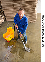 Smiling man moping warehouse floor - Portrait of smiling man...