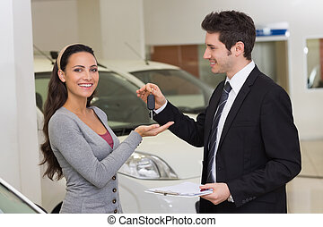 Smiling businessman giving car key to happy customer at new...