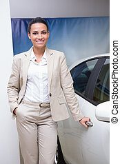 Smiling businesswoman holding a car door handles at new car...