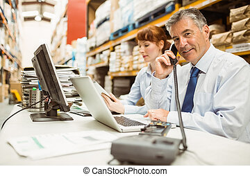 Manager working on laptop and talking on phone at desk in a...
