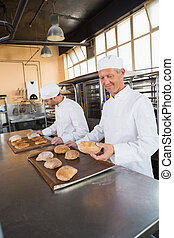 Bakers checking freshly baked bread in the kitchen of the...