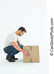 Delivery man crouching while picking cardboard box - Full...