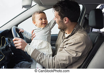 Father playing with baby in drivers seat in his car