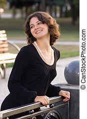 Dark hair girl in black dress posing outside