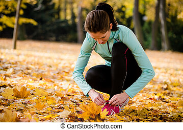 Woman tying shoelaces - jogging in nature - Young woman...