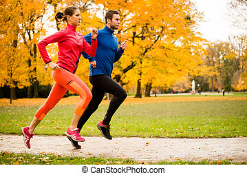 Couple jogging in autumn nature - Running together - friends...