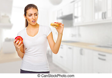 Girl with hamburger and apple ay kitchen - Young girl with...