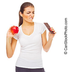 Young doubting girl with apple and chocolate