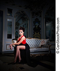 Woman sit on sofa at ancient room - Young woman sit on sofa...