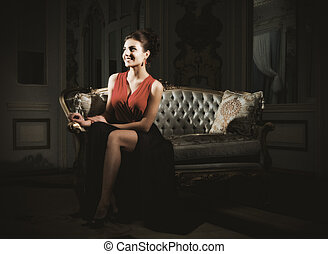 Young woman sit on sofa at ancient room (ancient version)