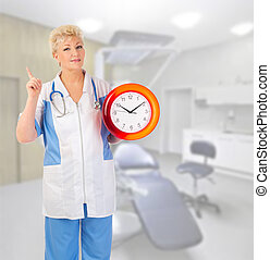 Smiling mature doctor with clock at medical office