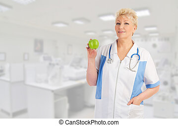 Mature doctor with green apple