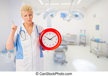 Mature furious doctor with clock at medical office