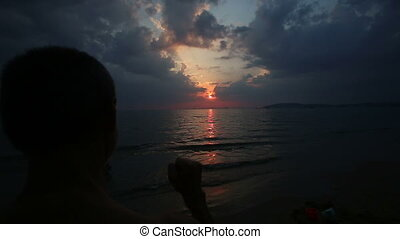 man raises his hand up in the sunset