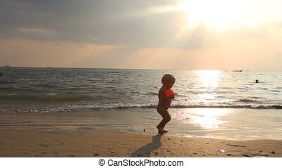baby girl walk on the beach at sunset - baby girl in purple...