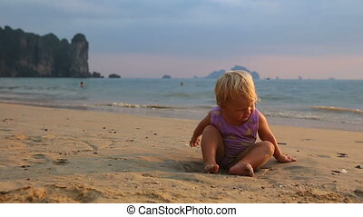 girl in purple swimsuit play on sand