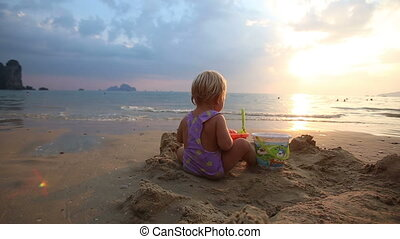baby girl in purple swimsuit play in the sand