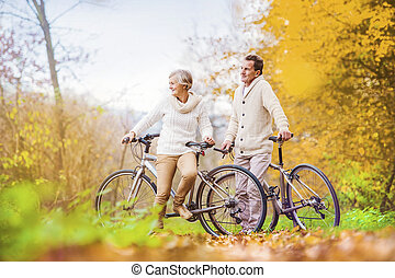 Active seniors riding bikes in autumn nature. They having...