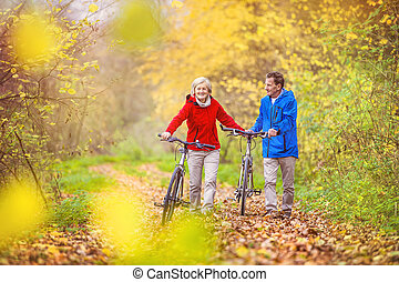 Active seniors walking with bike - Active seniors having...