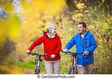 Active seniors walking with bike - Active seniors having...