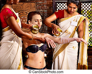 Woman having Ayurvedic spa treatment Pouring milk