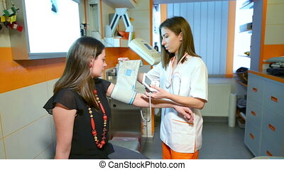 Measuring Blood Pressure - Assistant Doctor measuring blood...