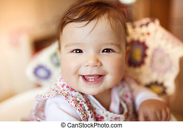 Happy smiling baby - Cute little baby sitting in a high...